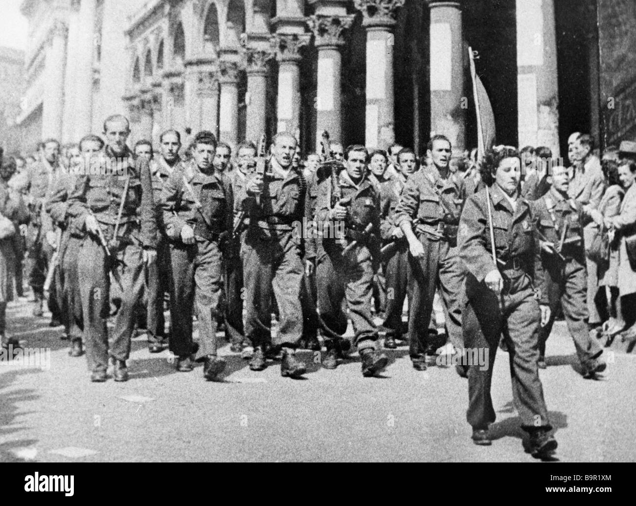 Armed group of the Resistance movement walking along a Milan street during WWII Stock Photo