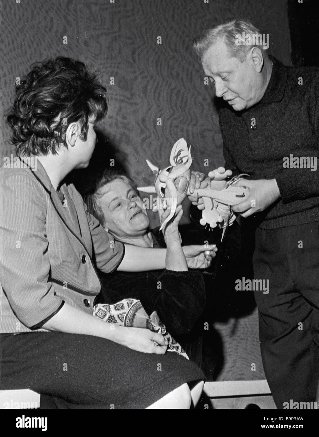 People s artist of the USSR Sergei Obraztsov right examining a puppet together with artists of the Moscow central - Stock Image