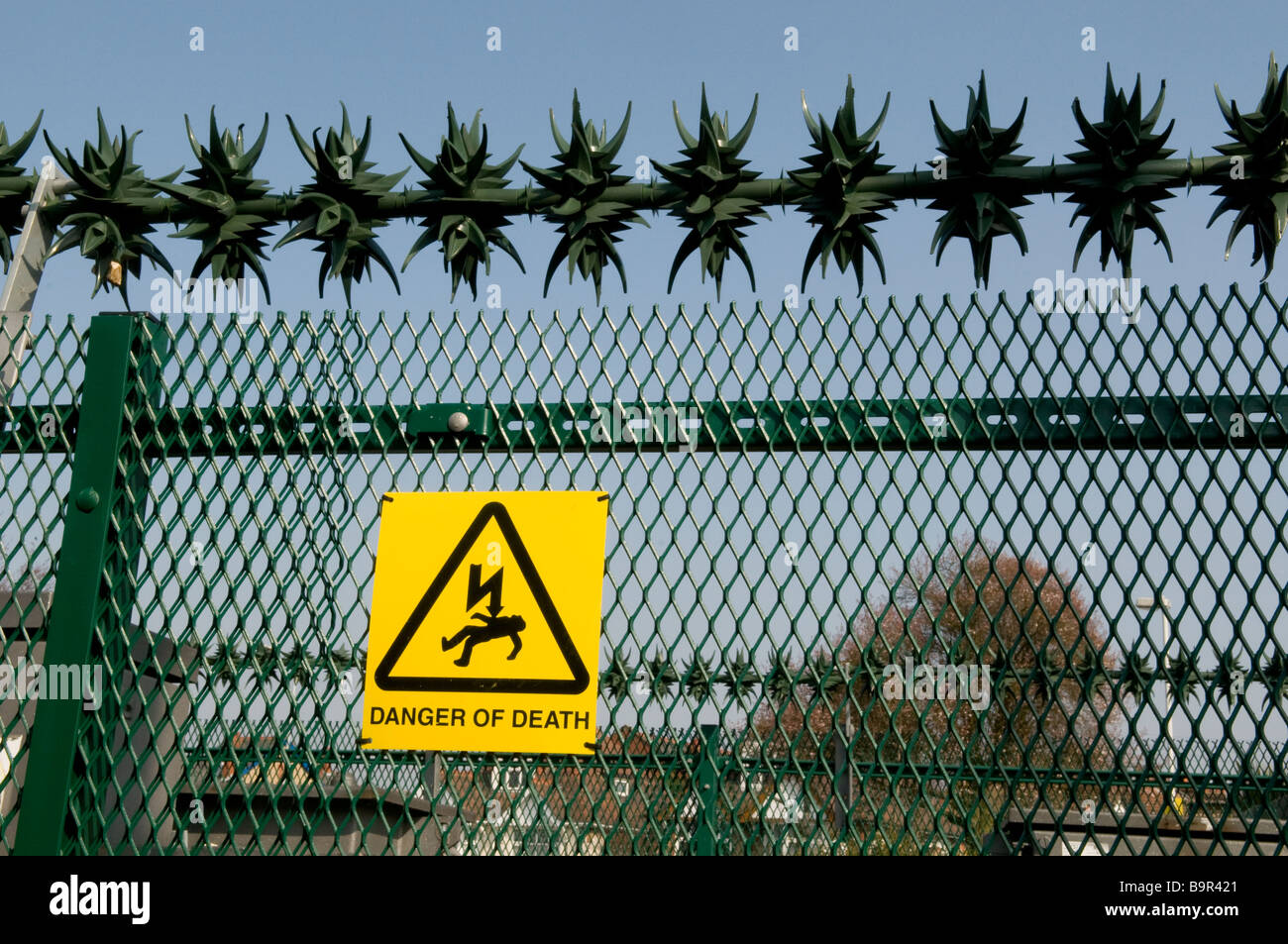 SECURITY FENCE AND WARNING SIGN ON AN ELECTRICITY SUB-STATION. SIGN READS DANGER OF DEATH. - Stock Image