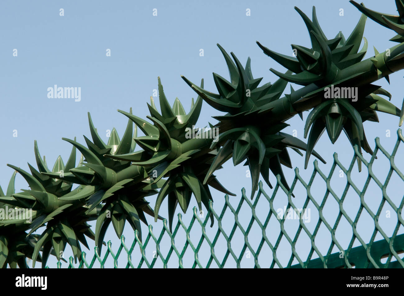 SECURITY FENCE MADE OF PLASTIC SPIKES ON AN ELECTRICITY SUB-STATION. SIGN ON FENCE READS DANGER OF DEATH. - Stock Image
