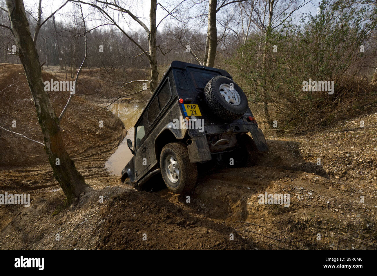 A Land Rover Defender 90 driving down a steep bank during an Off Road exercise Stock Photo