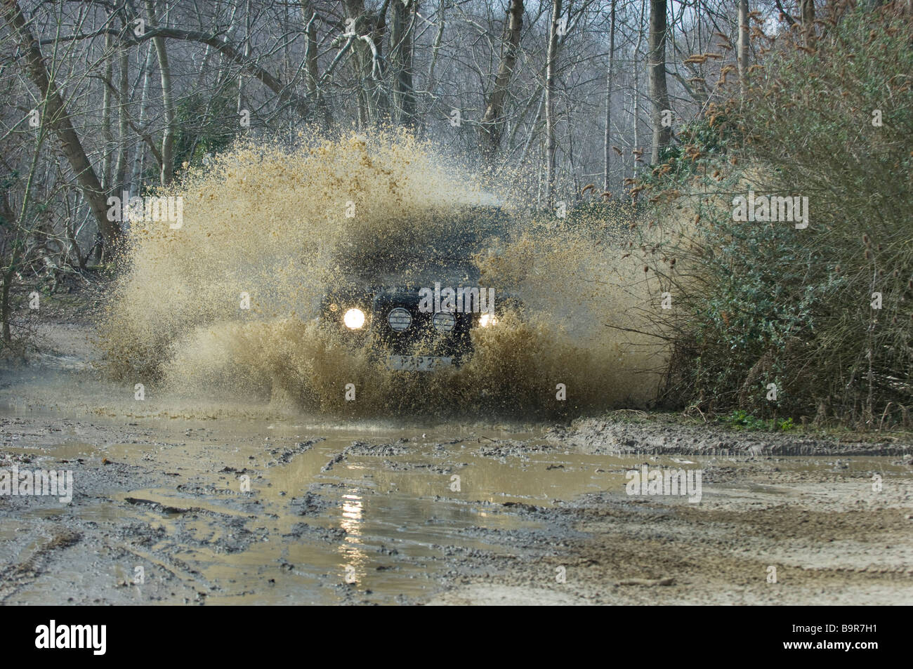 A Land Rover Defender 90 splashes through a flooded track in woodland in Slindon West Sussex UK during an Off Road - Stock Image