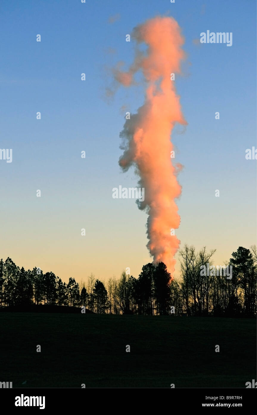 North Carolina factory smoke stack in the warm glow of the afternoon sunset - Stock Image