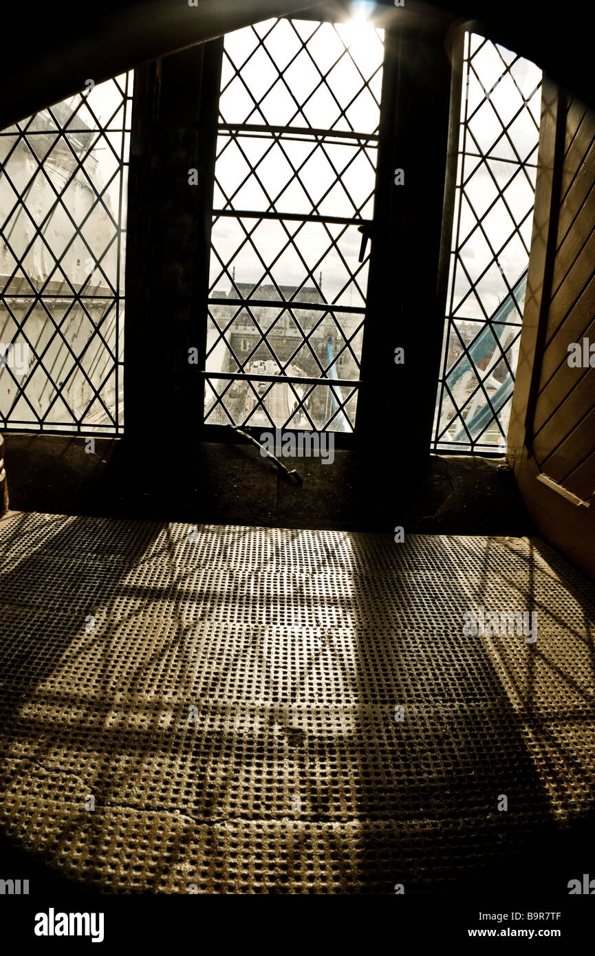 View through one of the victorian windows in one of the towers that comprise Tower Bridge in the  City of London. - Stock Image
