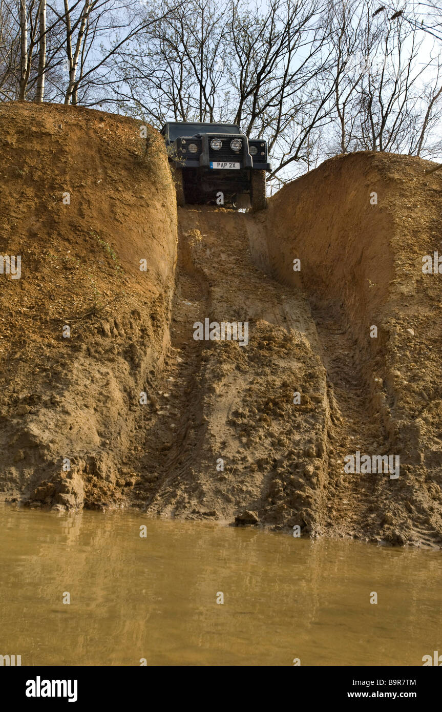 A Land Rover Defender 90 about to descend a steep hill into a river on an offroad driving track in Sussex UK. - Stock Image