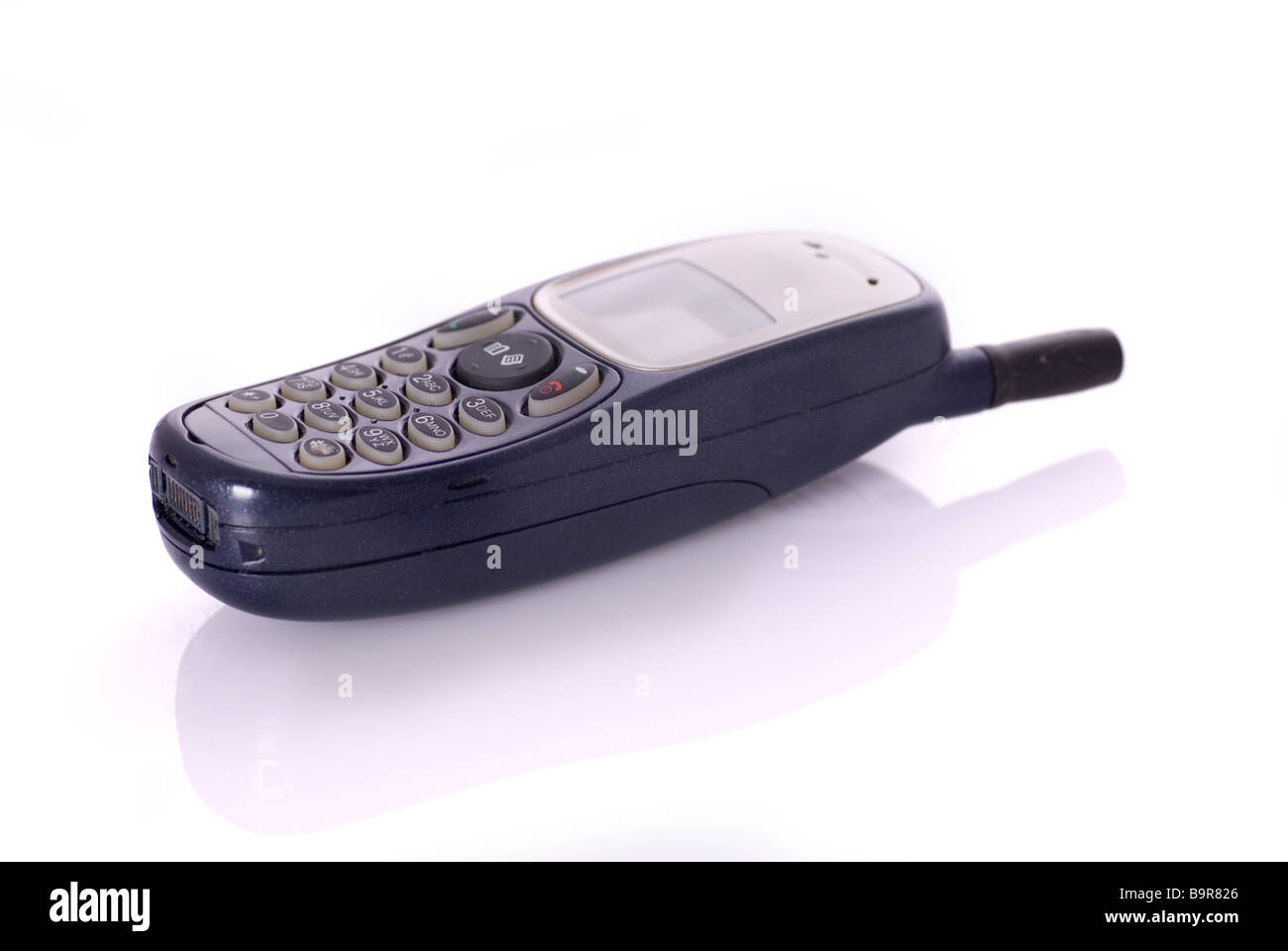 Still life image of an old fashioned mobile cell phone on a white background - Stock Image