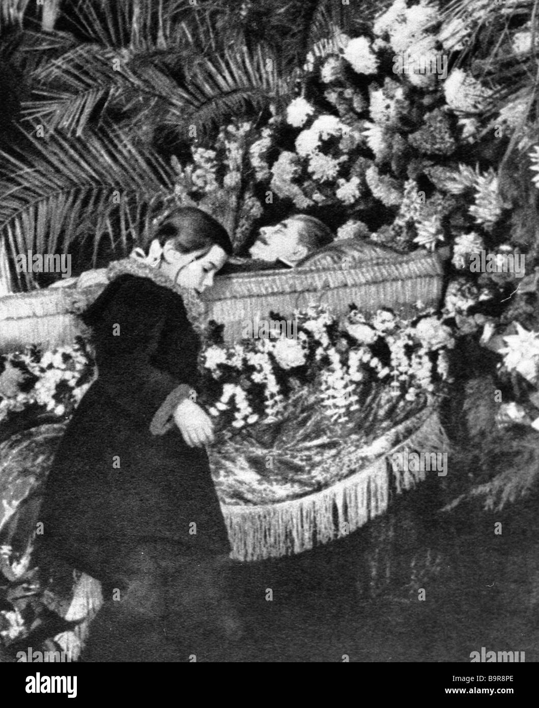 a girl laying flowers to the coffin with josef stalin s