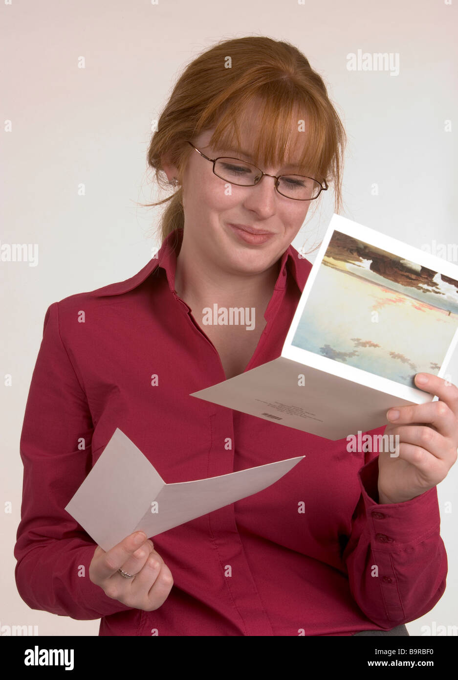 A woman reading a card that has conveyed some happy news that has made her smile - Stock Image