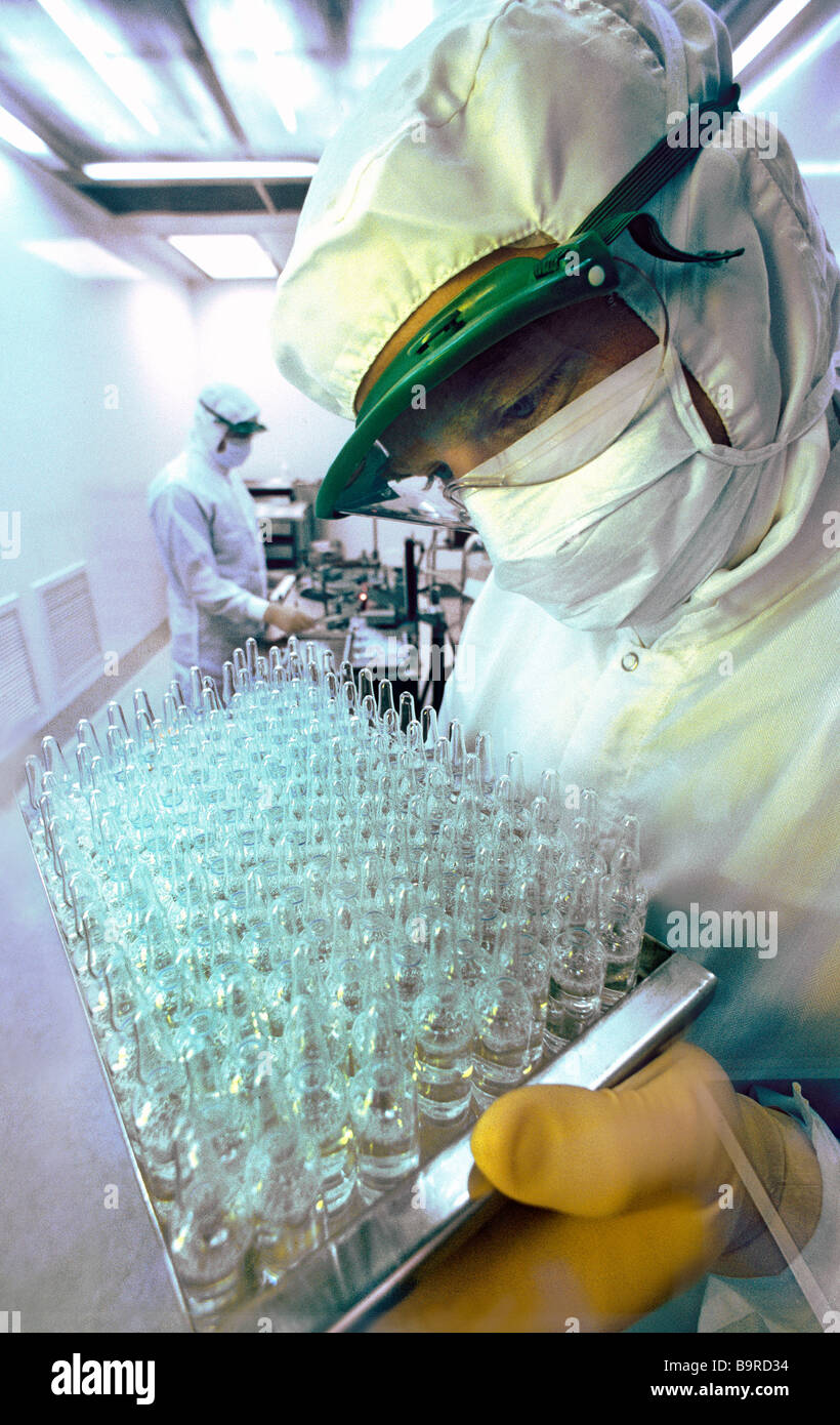 Lab technician wearing sterile suit holding tray of medicine ampules in highly sterile production laboratory. - Stock Image