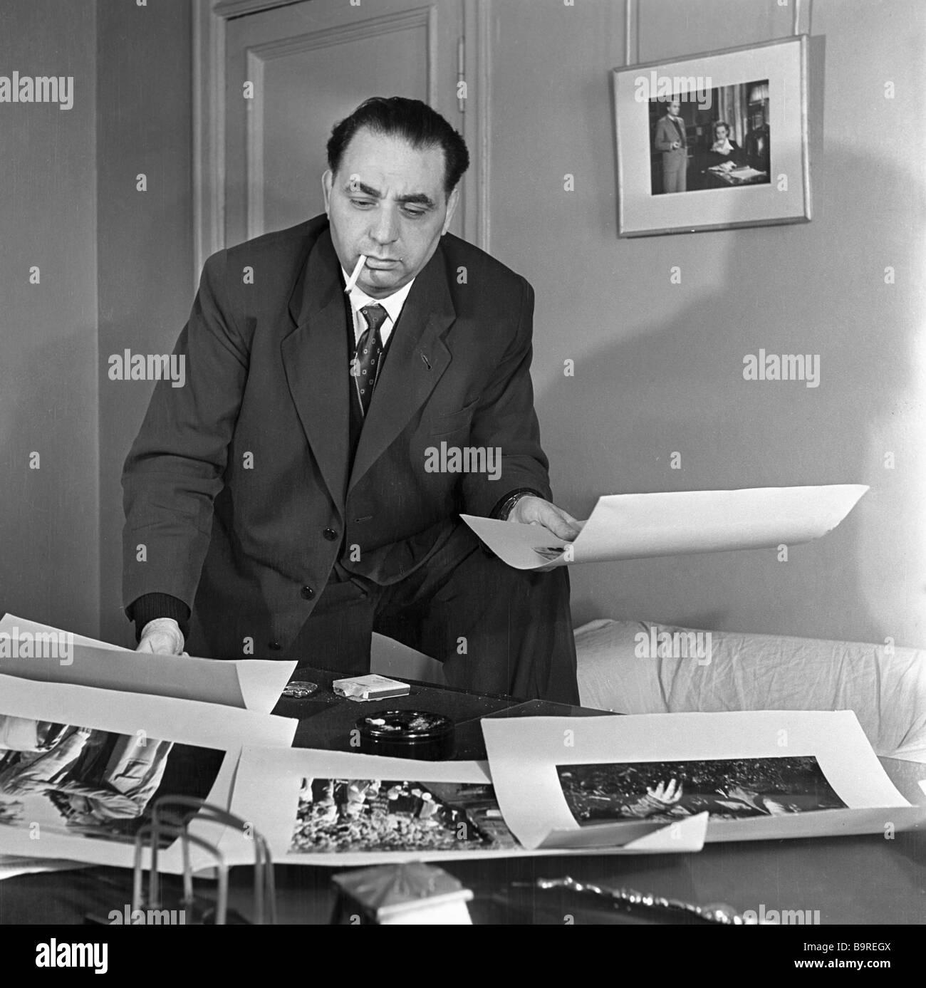 Film director Leonid Lukov examining photos - Stock Image