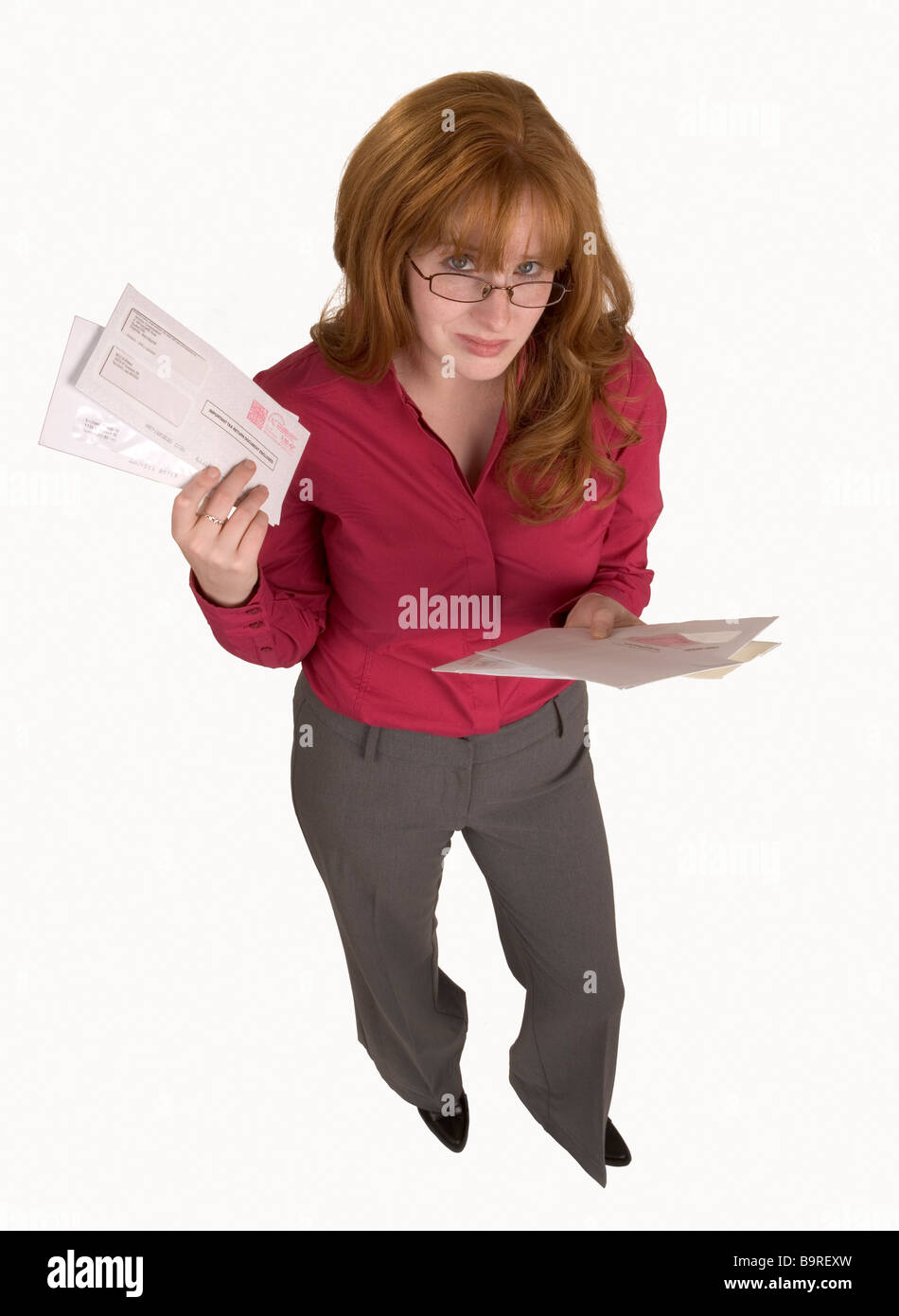 A woman holds many bills that have just arrived in the mail - Stock Image