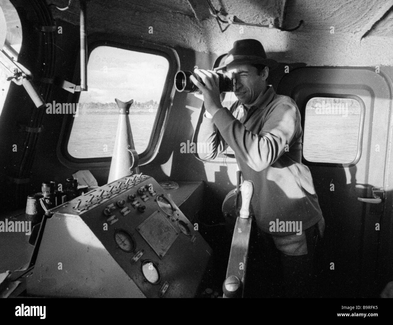 A fishing inspector in his boat watches the river with a spy glass Stock Photo