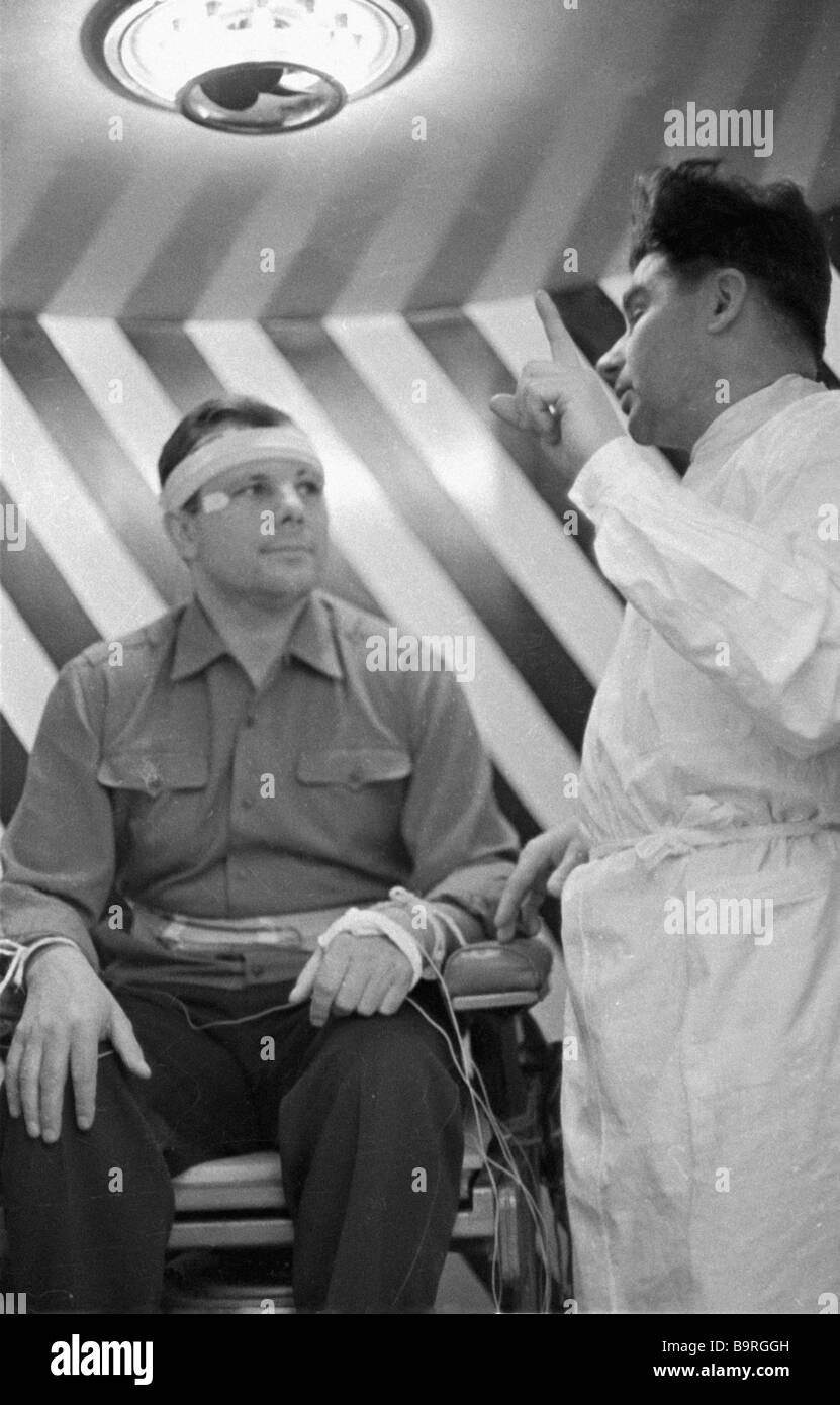 Space pilot Yuri Gagarin left listens to the doctor s advice during training - Stock Image