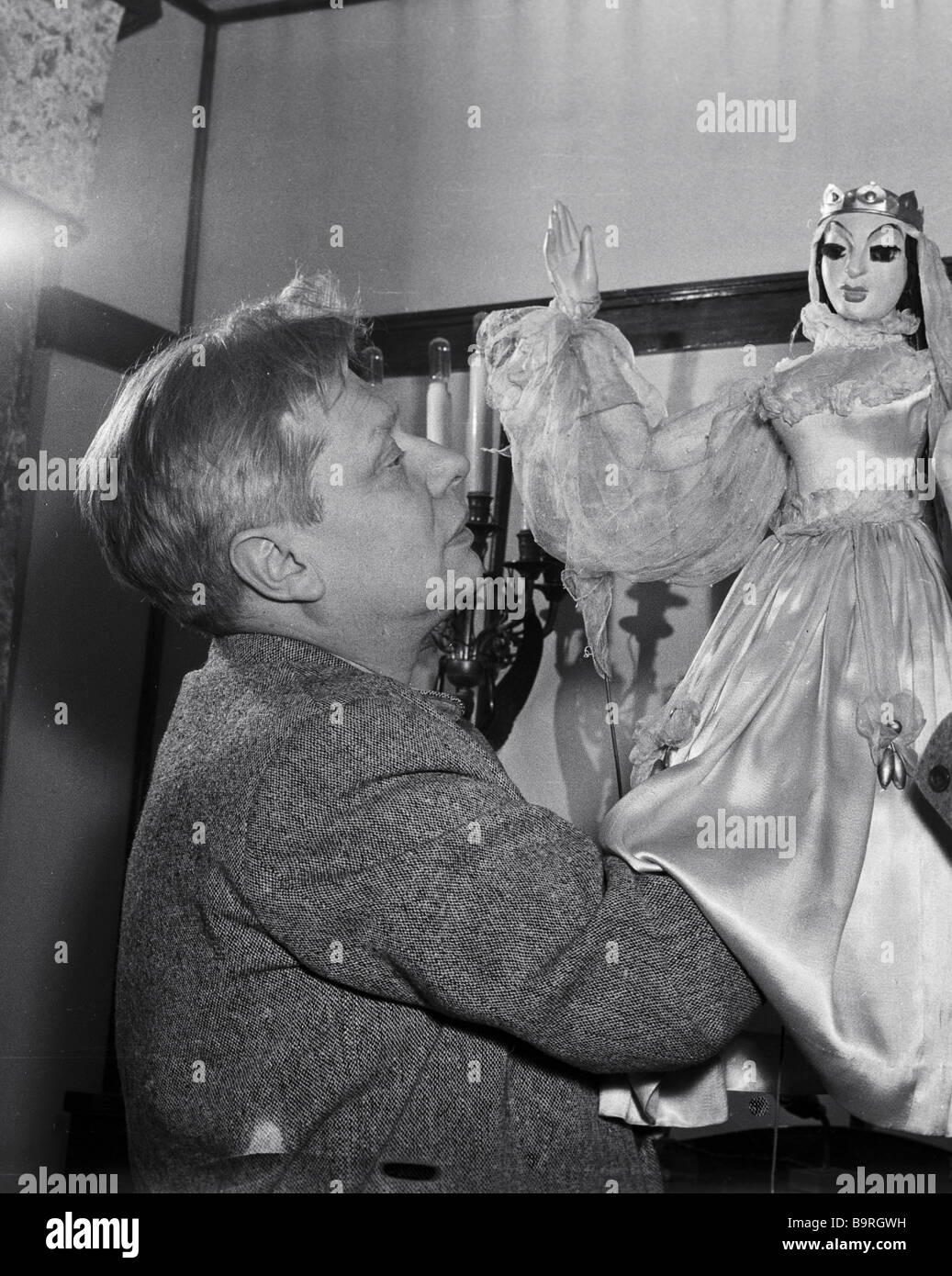 Sergei Obraztsov artistic director of the Central Puppet Theater examining a new puppet in the theater s workshop - Stock Image
