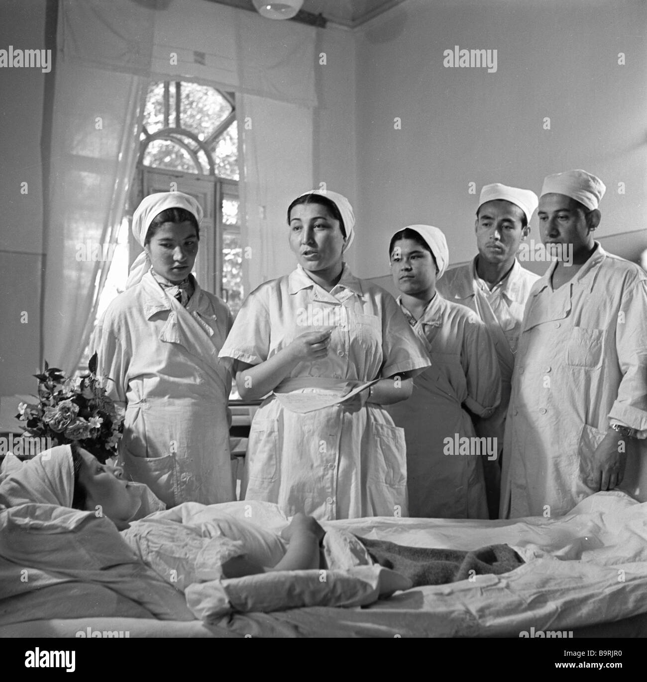 A doctor accompanied by a group of students making a hospital round - Stock Image