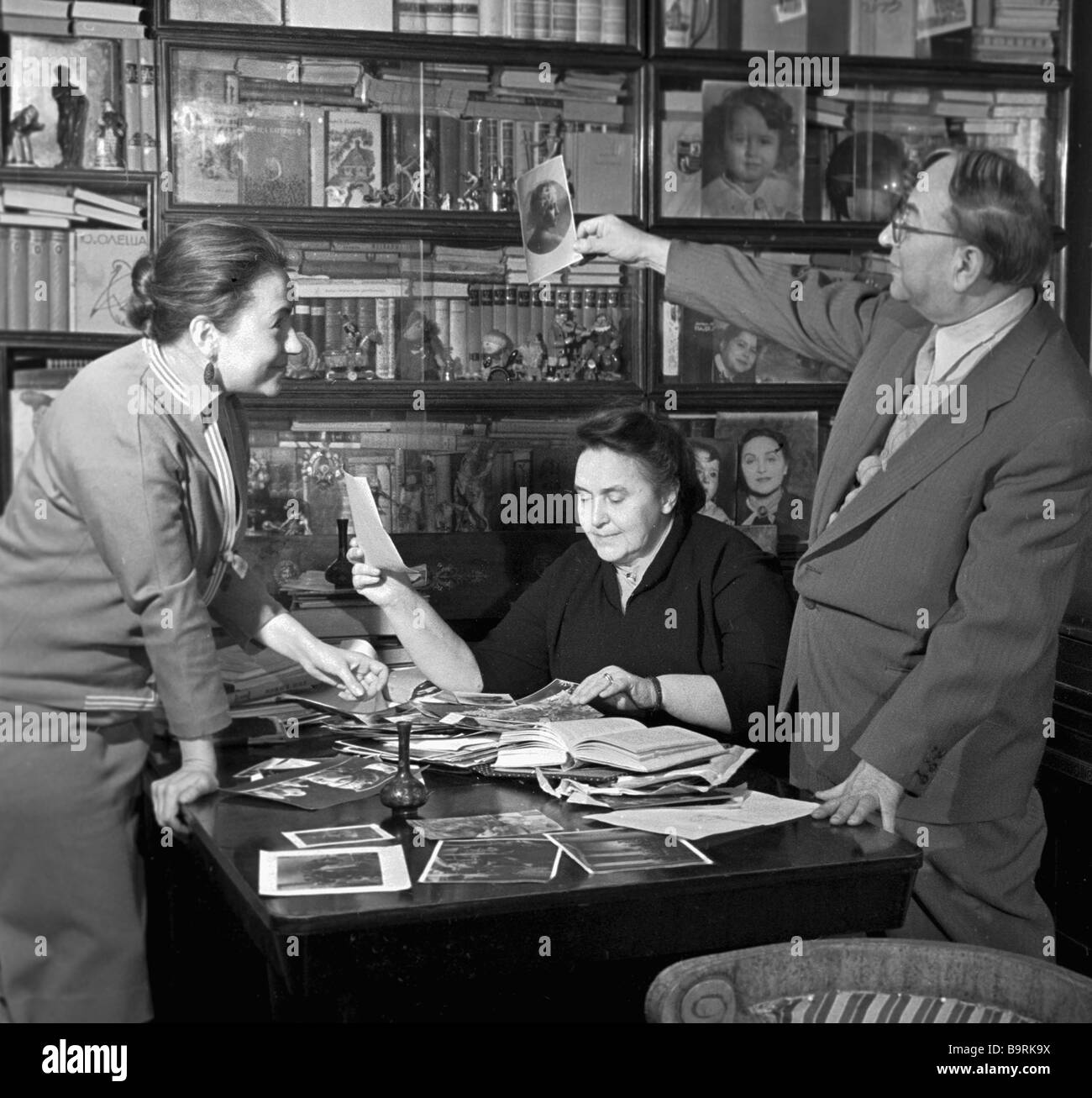 Film maker Grigory Roshal his daughter Marianna and his wife Vera Stroyeva going through the family photos - Stock Image