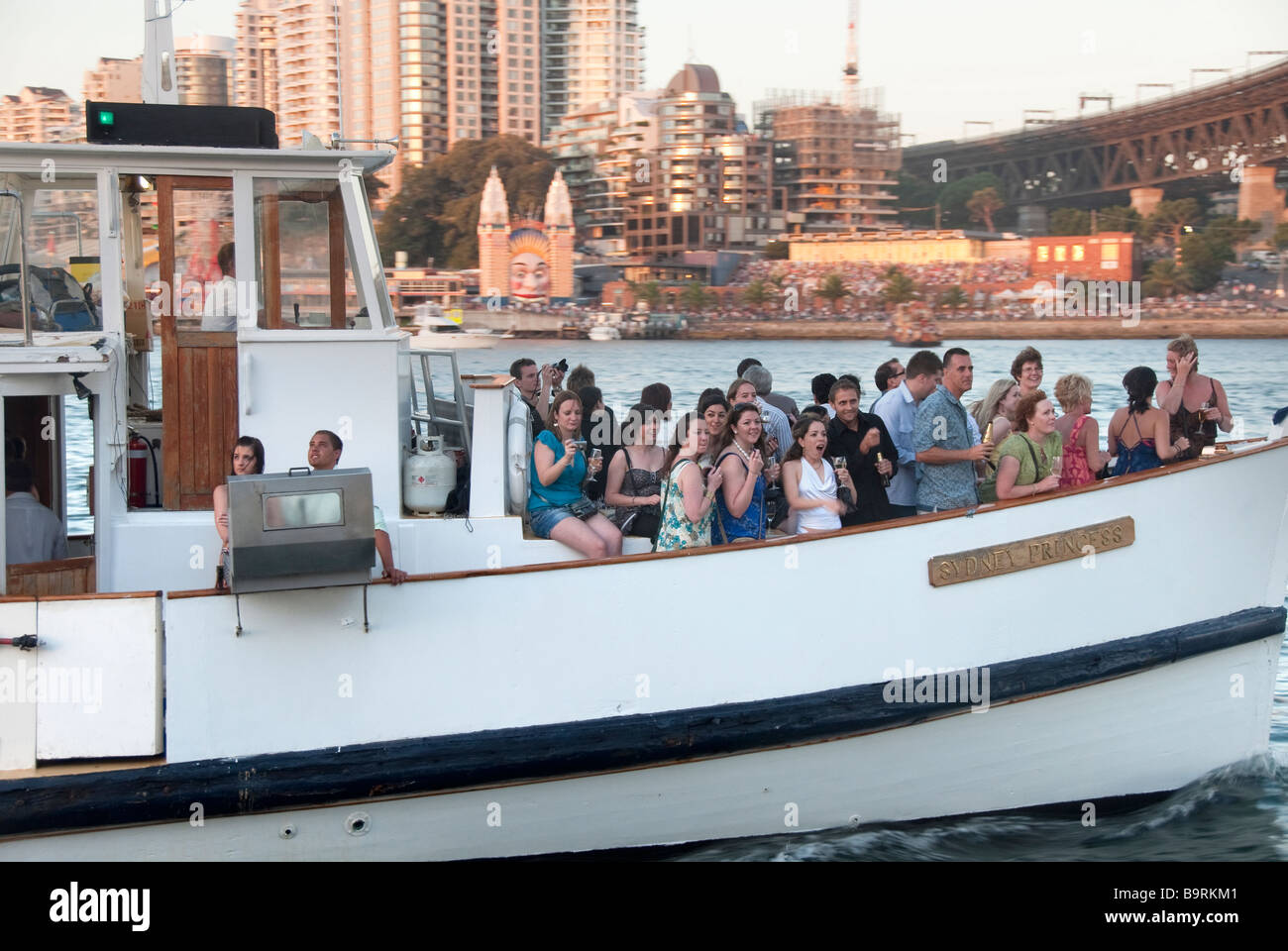 Revellers aboard a tug boat on Sydney Harbour New Year's Eve with Luna Park and Milsons Point in the background - Stock Image