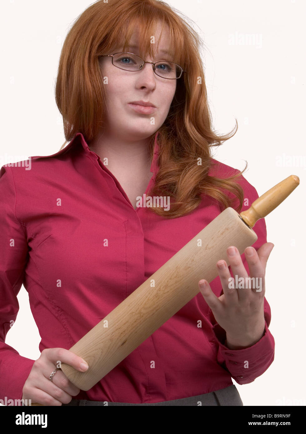 An angry redheaded woman with a wooden rolling pin holing it in a menacing way - Stock Image