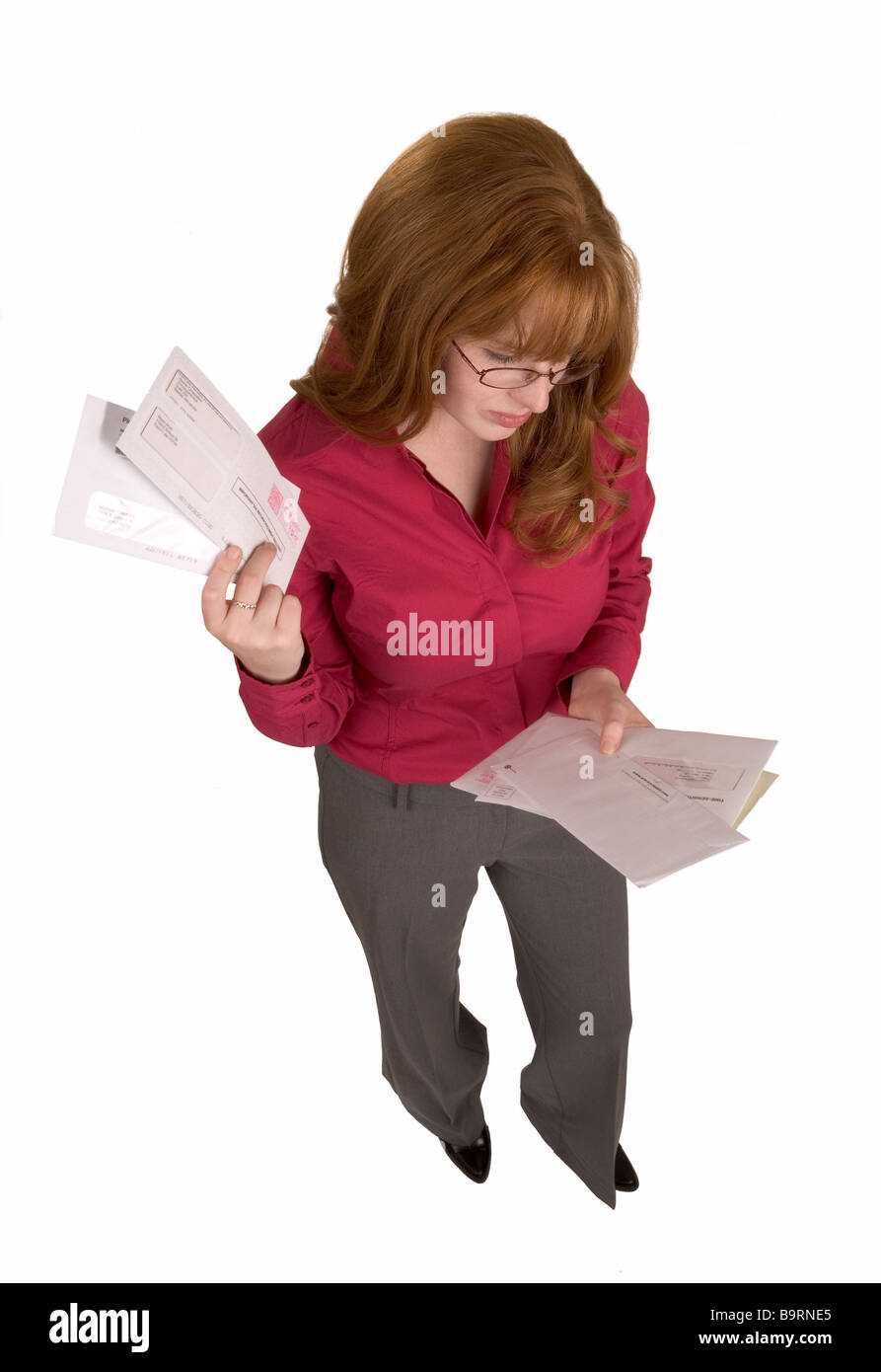 A woman holds many bills or letters that have just arrived in the mail - Stock Image