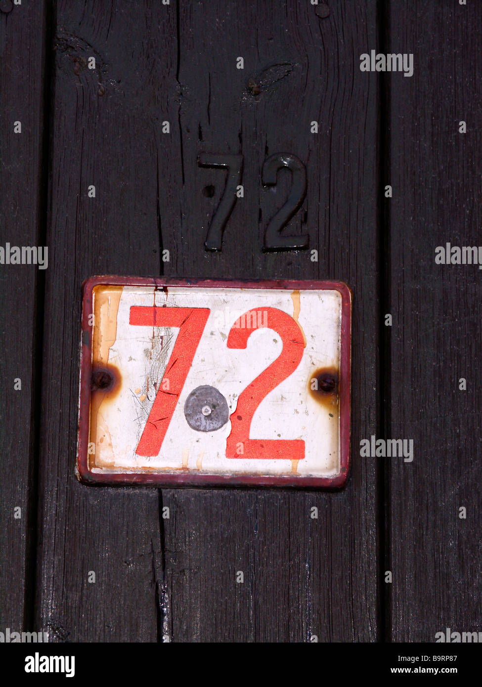 Numer 72 sign on old door - Stock Image