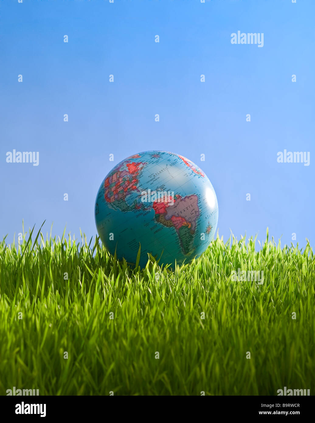 globe in grass with sky - Stock Image