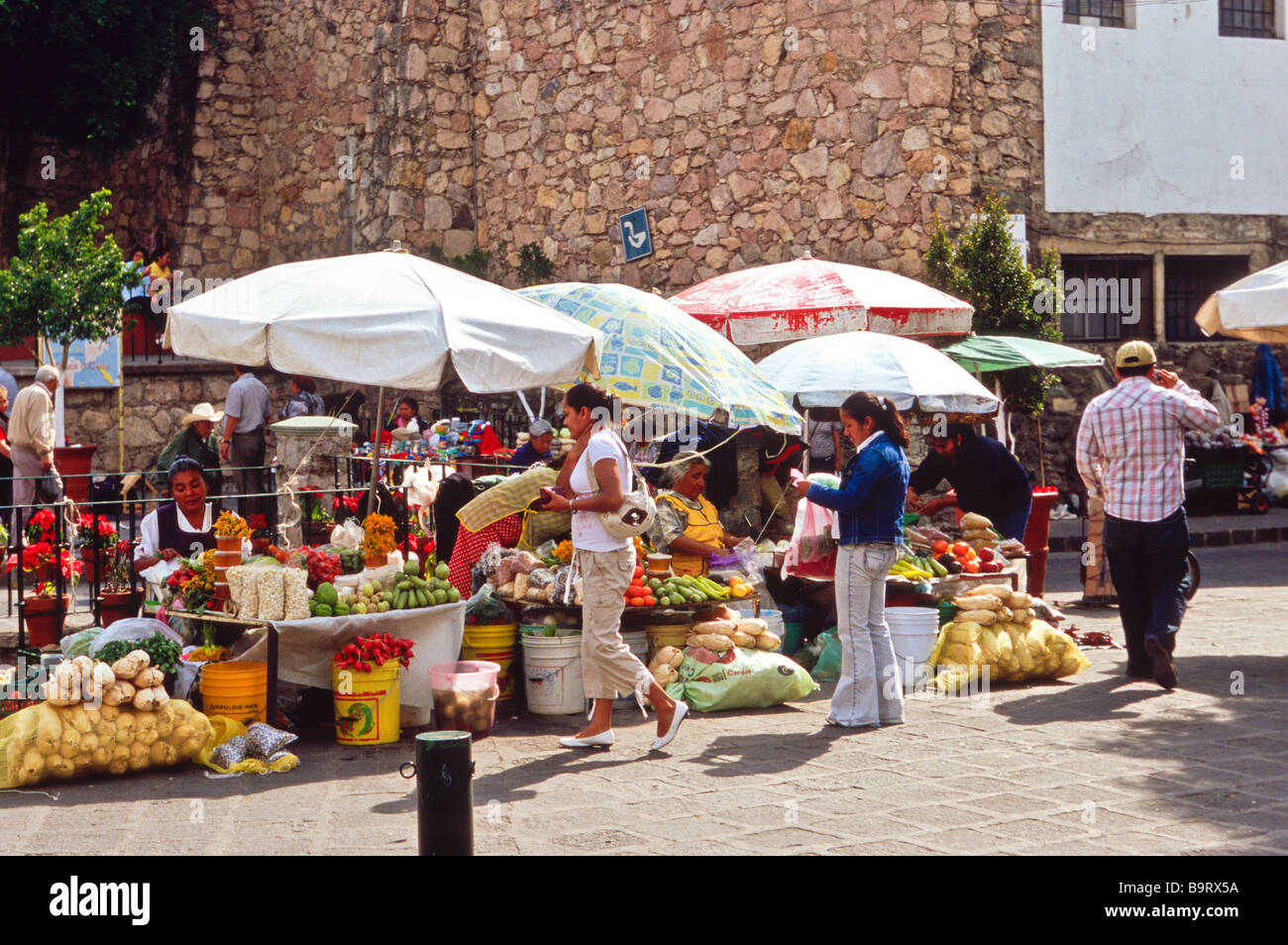 Mexican men and women, at the market, selling vegetables, nuts and fruits on a street in the colonial city of Guanajuato Stock Photo
