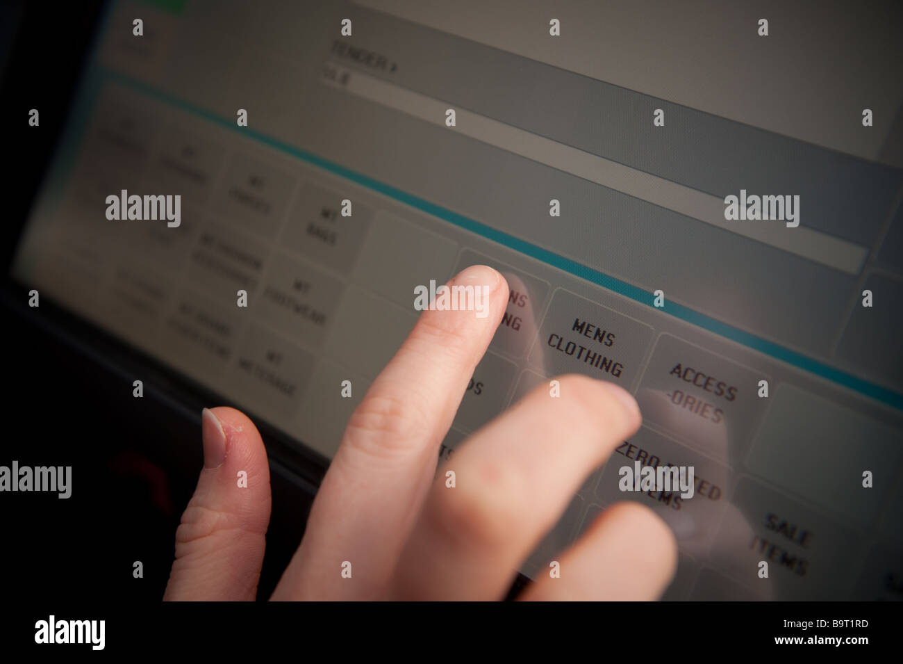 Shop assistant using touch sensitive screen checkout till in a shop - Stock Image