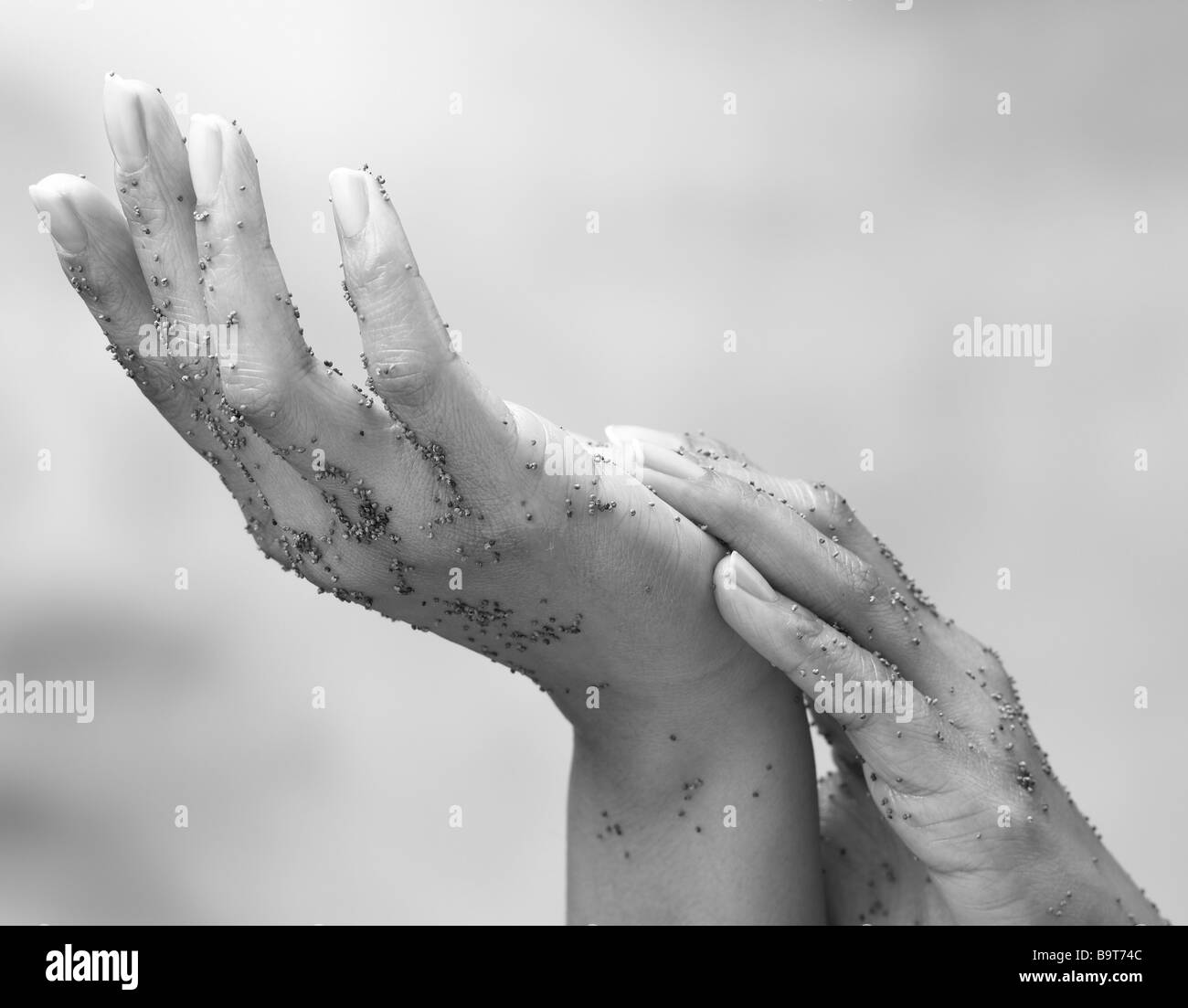 pair of hands rubbing exfoliator in during a beauty treatment - Stock Image