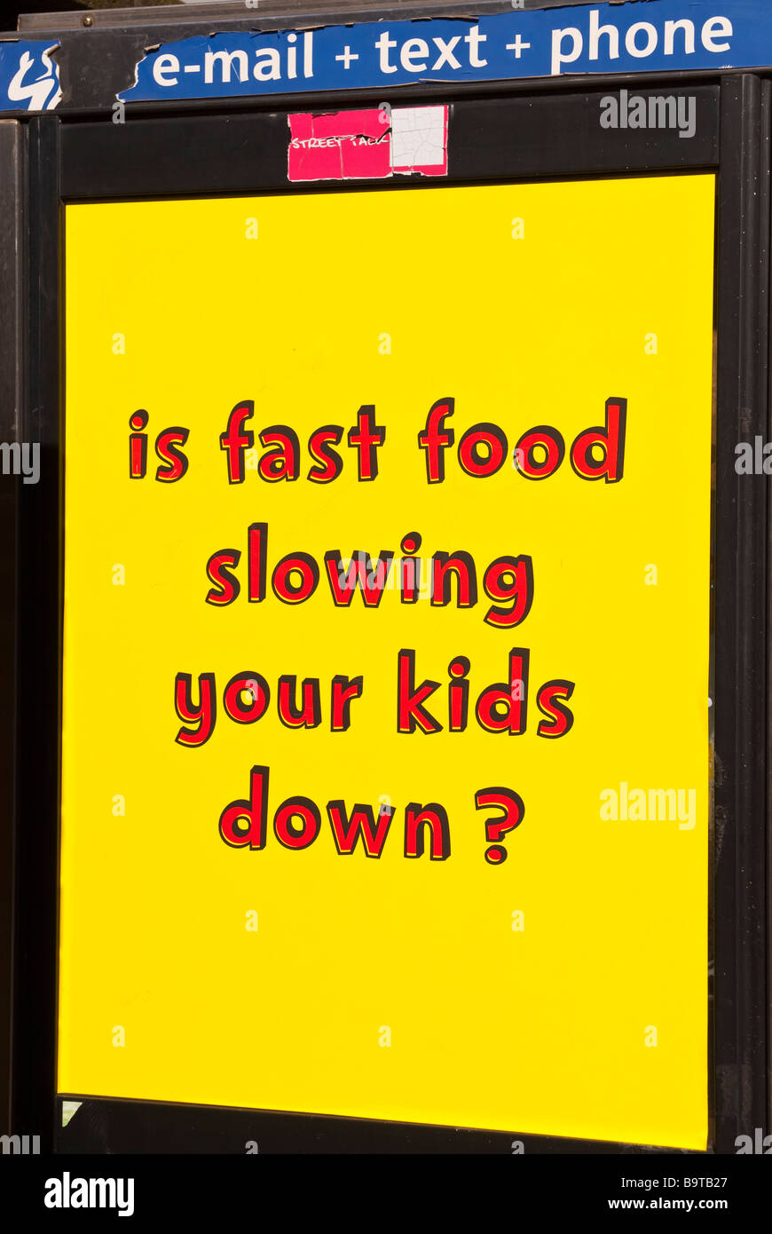 A sign on a phonebox warning of kids eating junk food - Stock Image