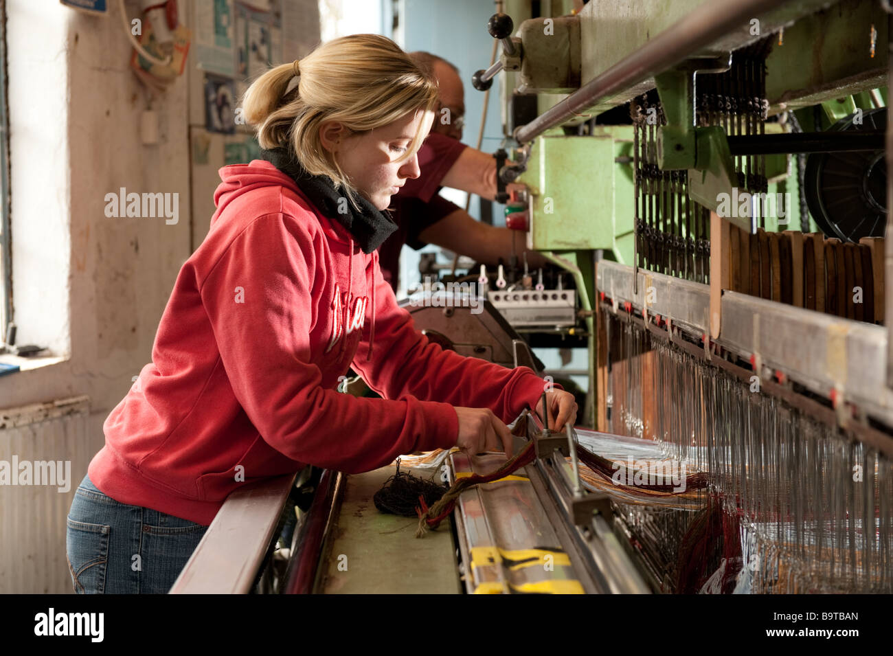 A young woman setting up yarns on the the weaving loom at Melin Tregwynt welsh woollen mill Castlemorris Pembrokeshire - Stock Image