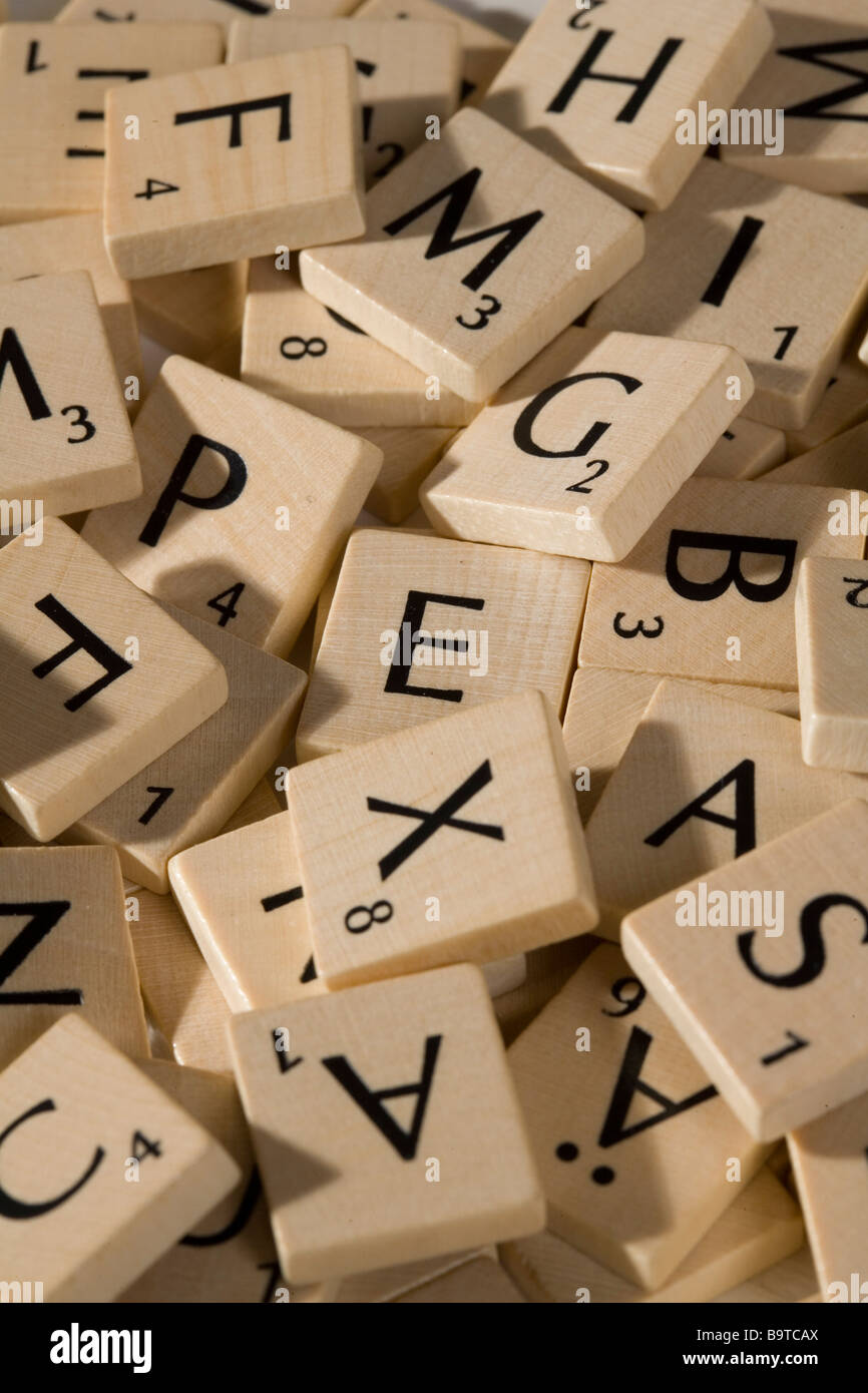 Scrabble pieces with numerous different letters - Stock Image