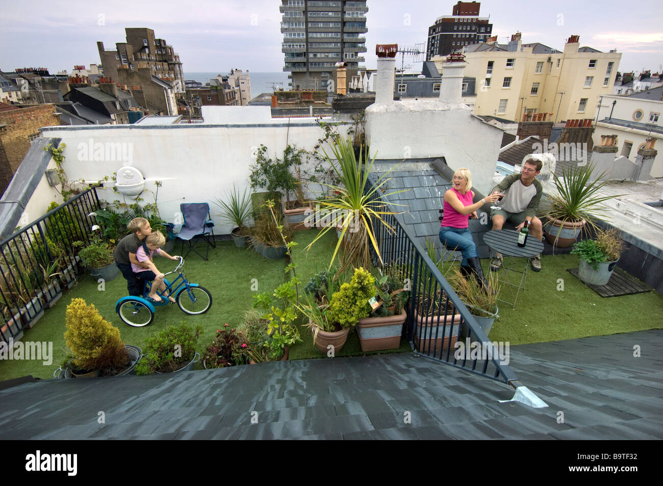 A family on the roof garden of their town centre center house in Brighton UK - Stock Image
