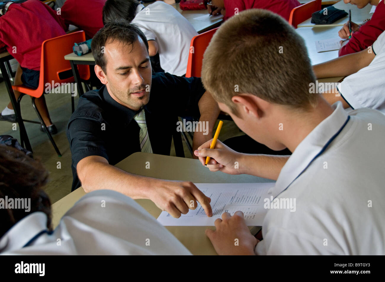 Male teacher coaching teenage boy student with his study work in secondary high school classroom - Stock Image