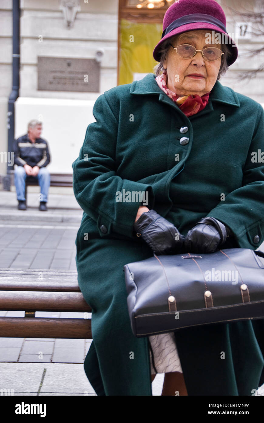 Woman seating on a bench in the streets of Vilnius looking at the camera. Man in the background, Vilnius, Lithuania, - Stock Image