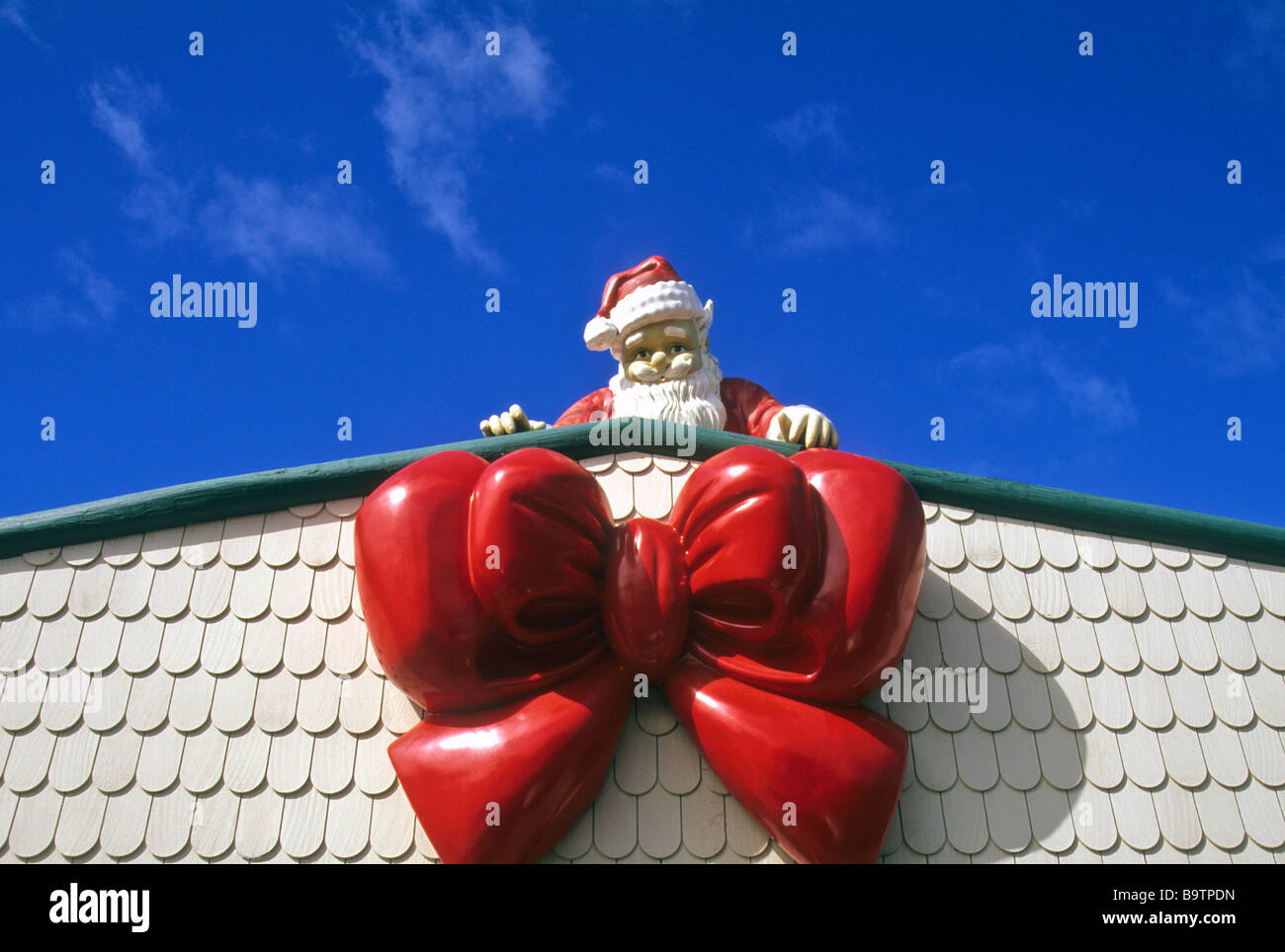 Santa Claus Figure And Giant Bow On The Roof Of Christmas Cottage Stock Photo Alamy