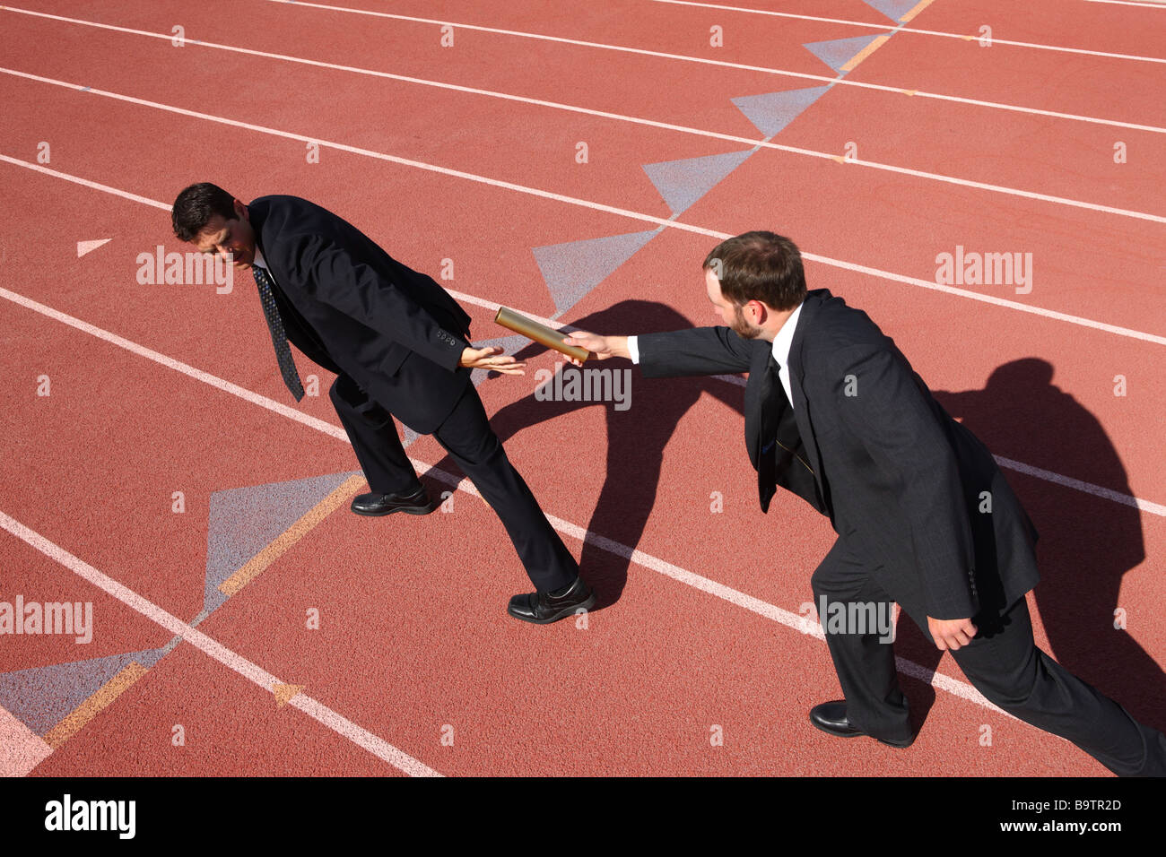Businessmen hand baton in track race - Stock Image