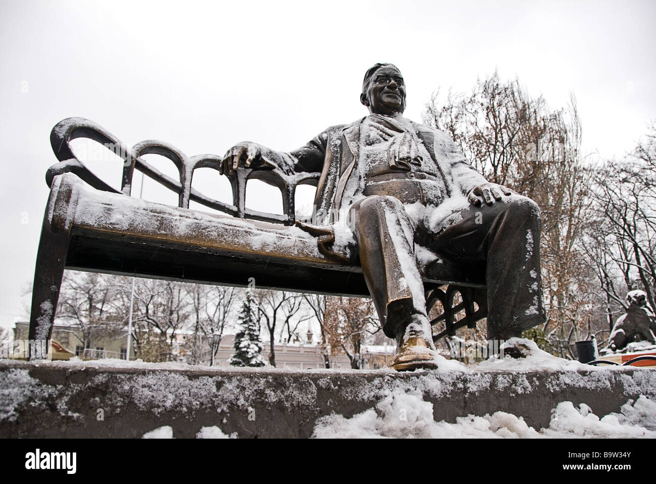Statue of a man sitting on a bench full of snow, Odessa, Ukraine, Europe Stock Photo