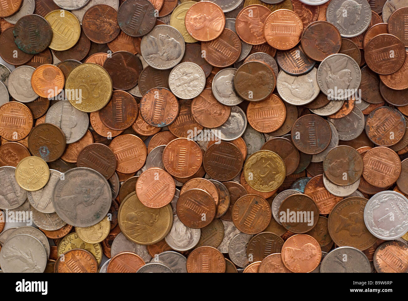 a layer of coins of multiple currencies - Stock Image