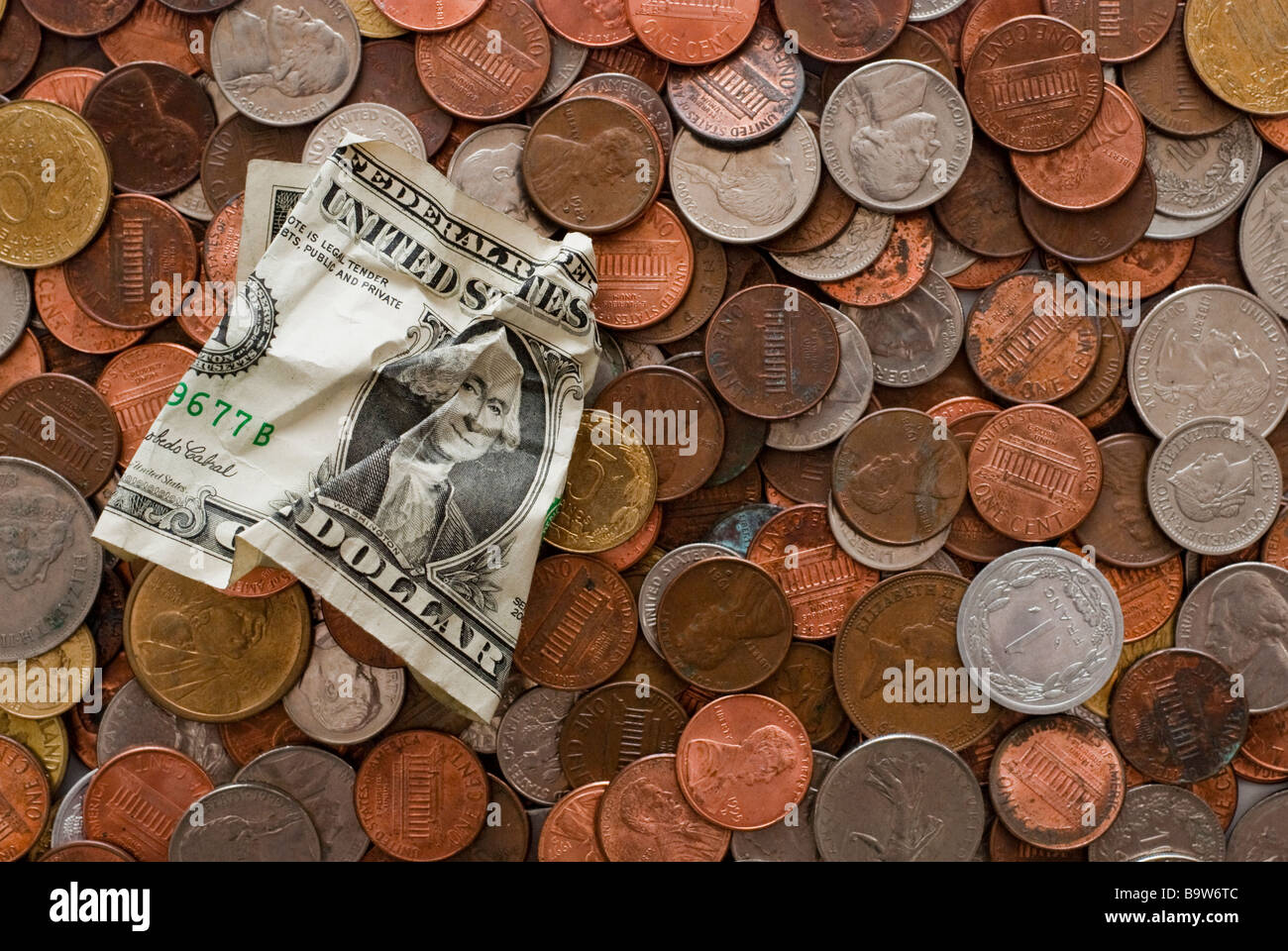 A crumpled dollar bill on top of a layer of coins of multiple currencies - Stock Image