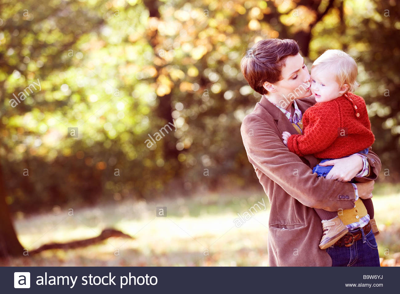 A young mother kissing her baby tenderly on the cheek - Stock Image