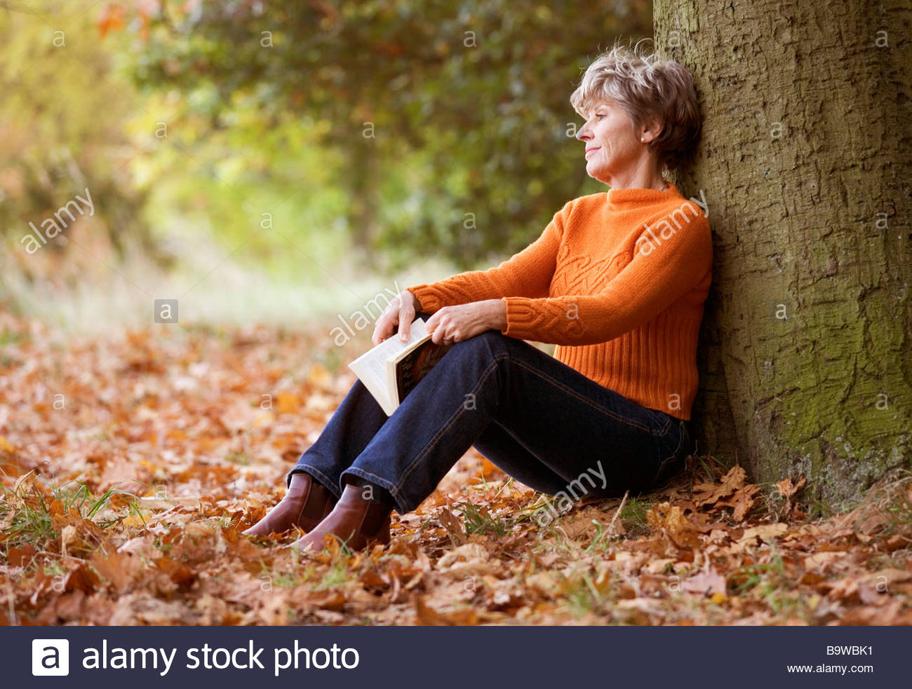 A senior woman sitting beneath a tree looking thoughtful - Stock Image