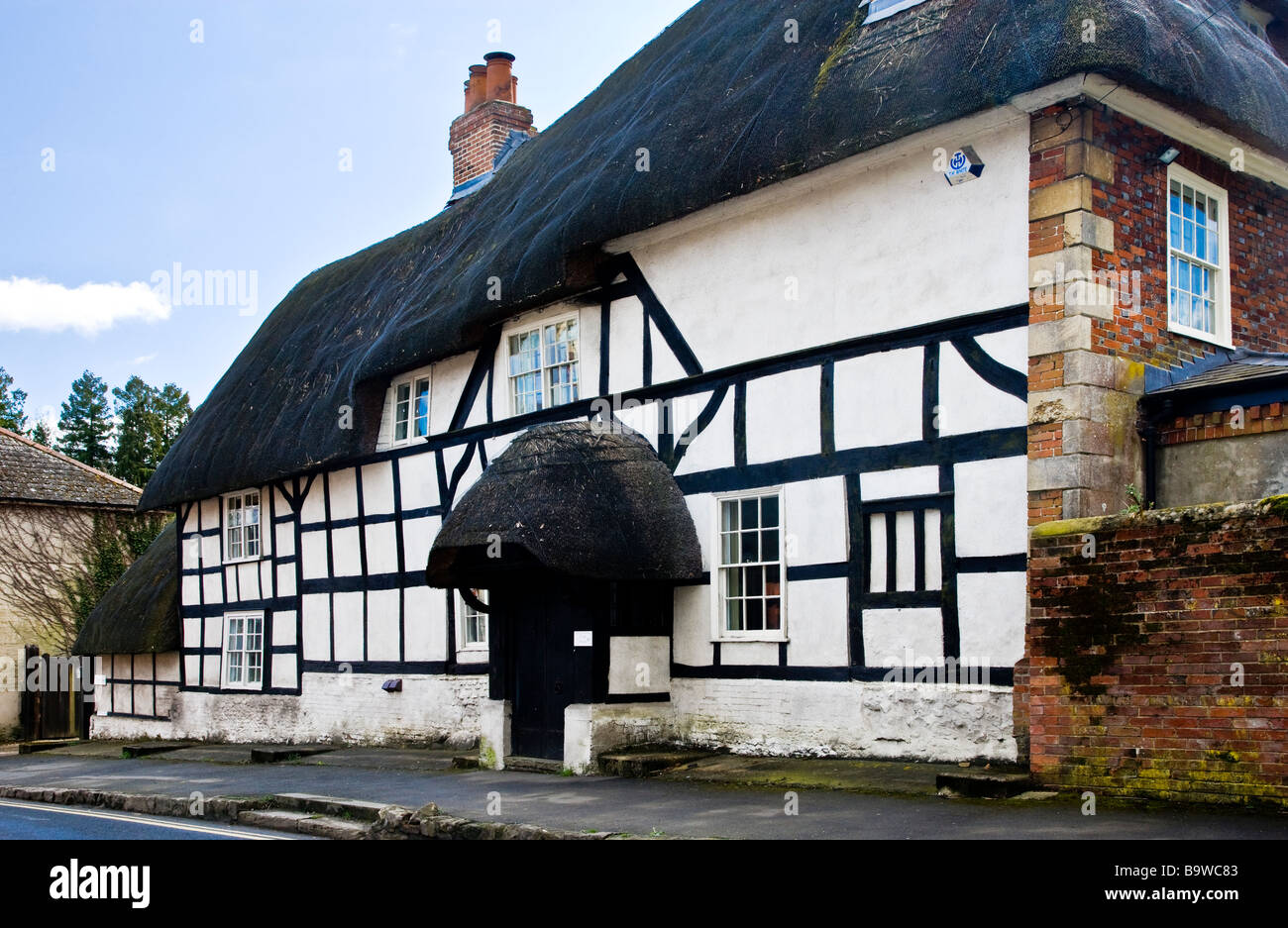 An old thatched timber framed Tudor cottage in the English village of Pewsey in Wiltshire England UK - Stock Image
