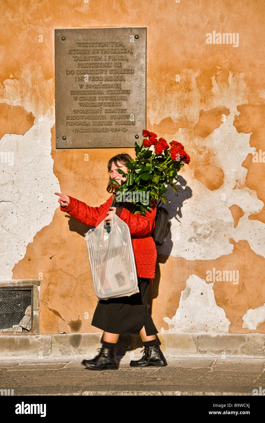 Woman with a flower bouquet walking in the streets of the old city of Warsaw, Poland, Europe. - Stock Image