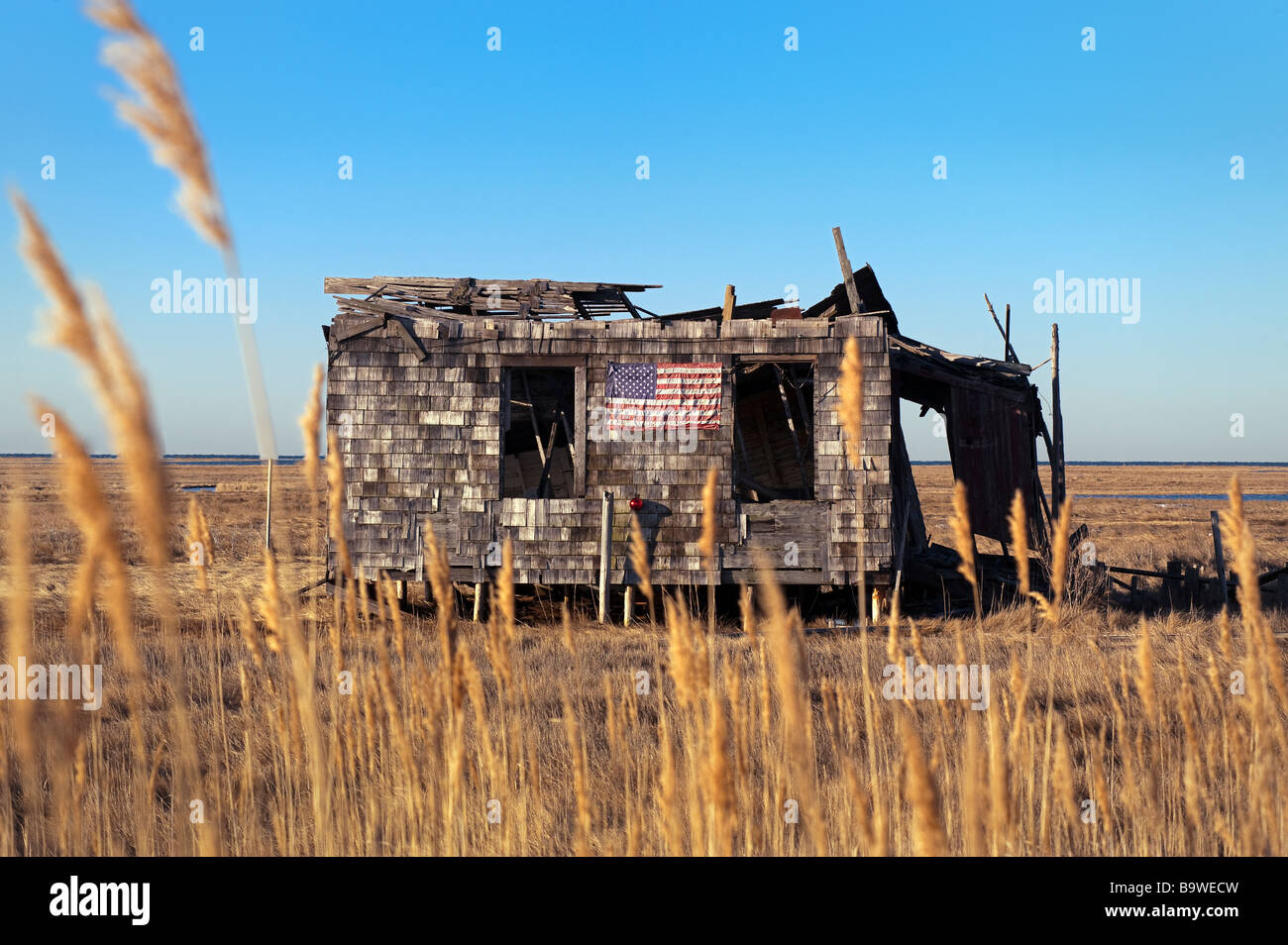 Ruined and abandoned shack with American flag and Christmas wreath - Stock Image