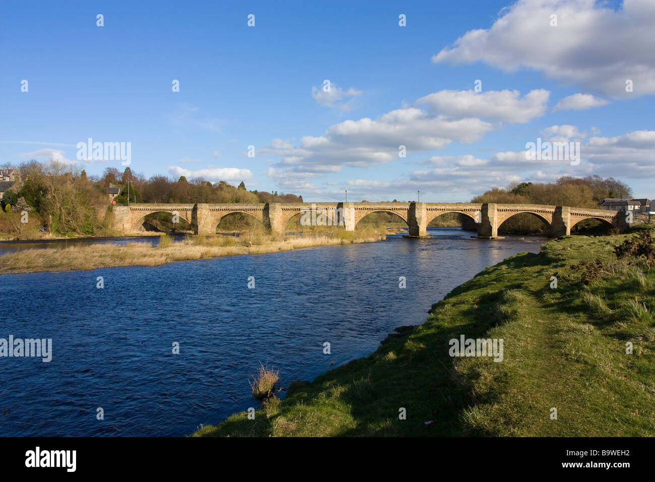 Wide landscape view of the historic old bridge spanning the slow moving river Tyne at Corbridge Northumberland - Stock Image