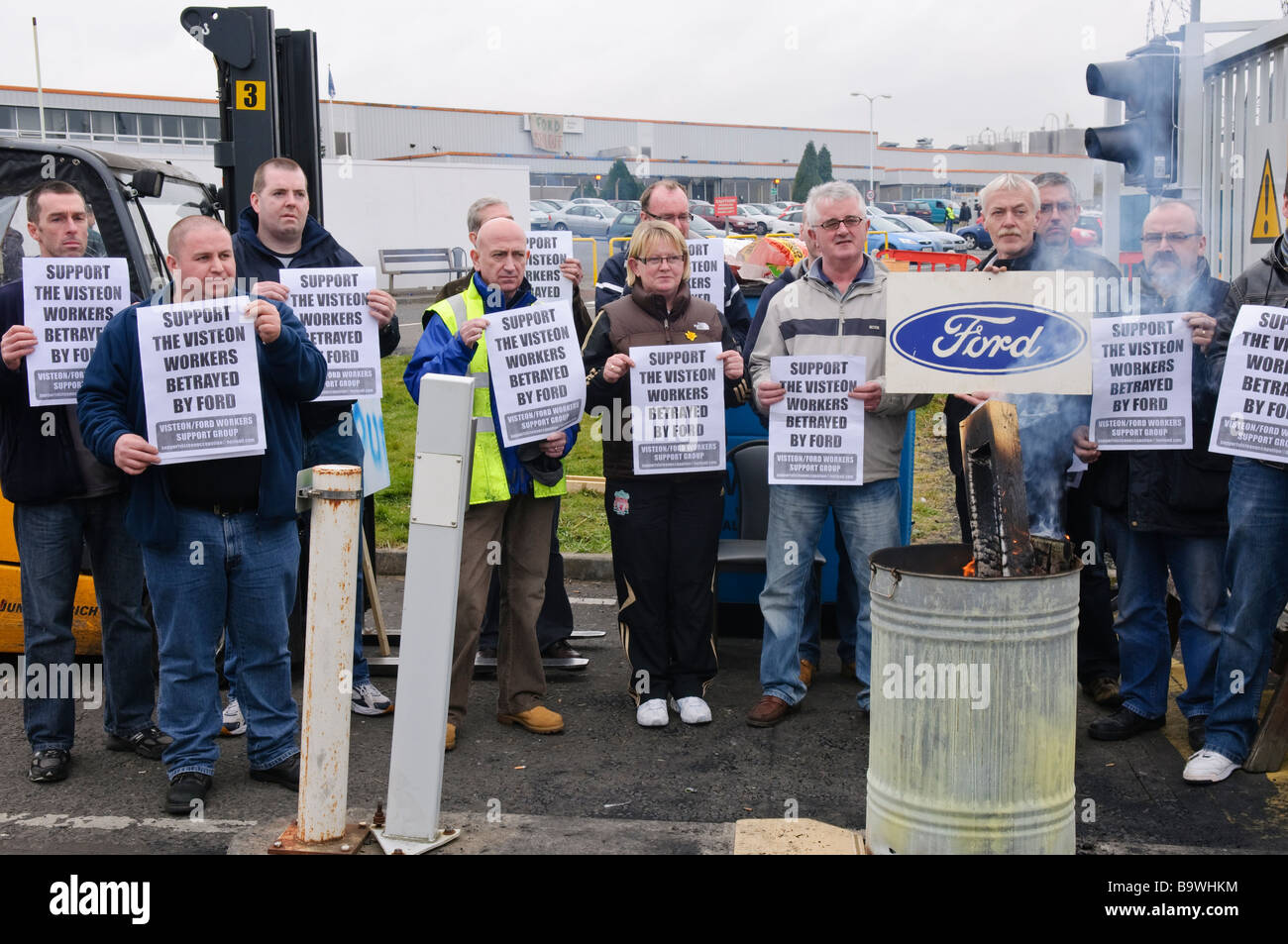 Workers demonstrate against redundancies at a Ford factory by holiding up posters asking for support. - Stock Image