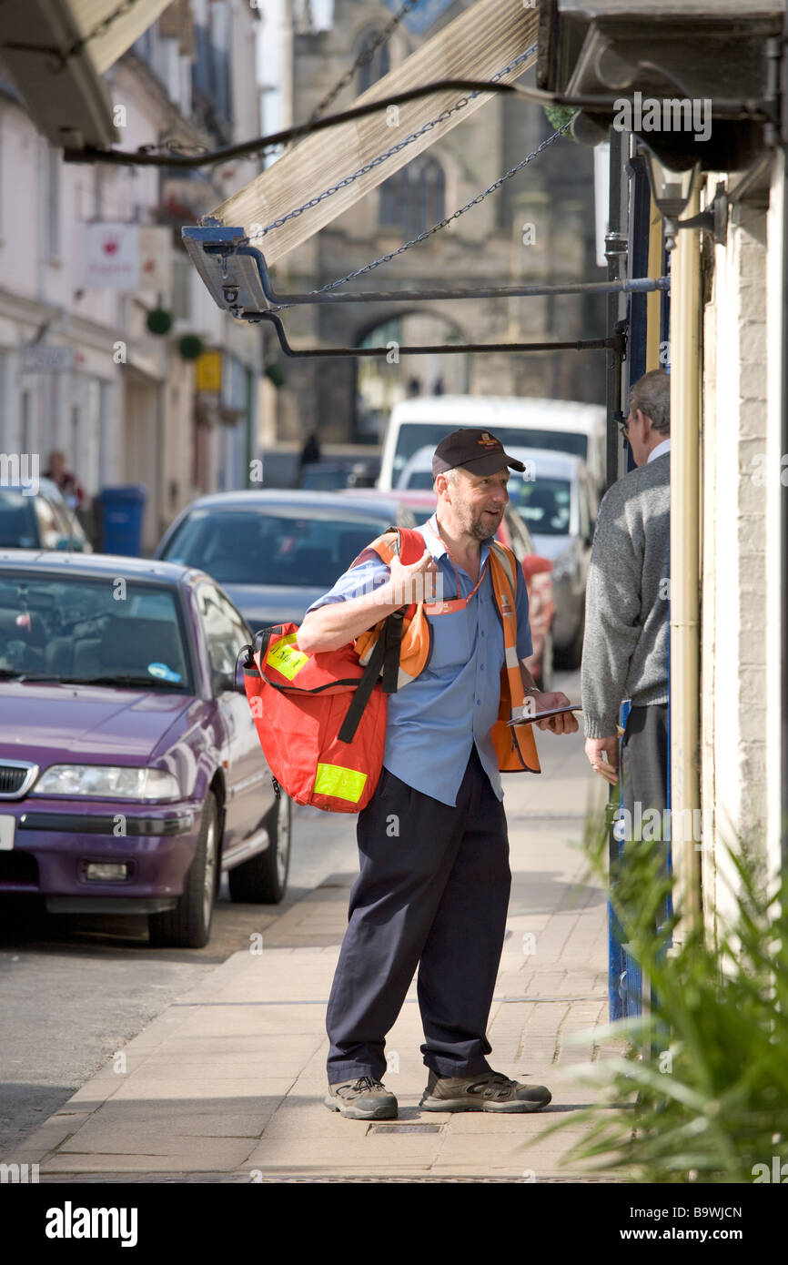 Royal Mail postman delivers letters and speaks to a shop owner in the historic town of Warwick, Warwickshire, UK. - Stock Image