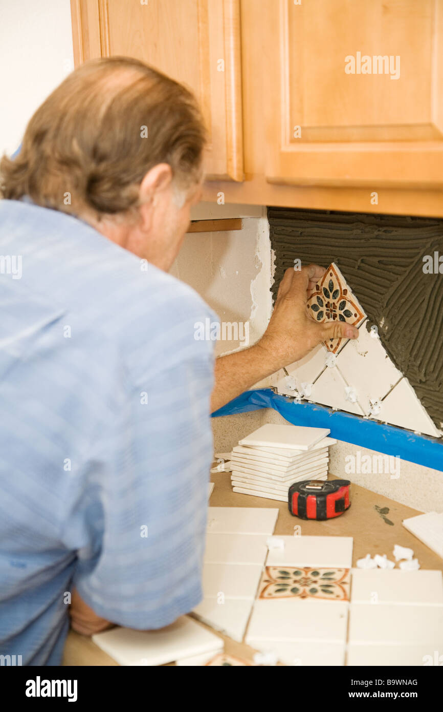 Tile setter uses spacers to carefully apply tiles to the wall Stock ...
