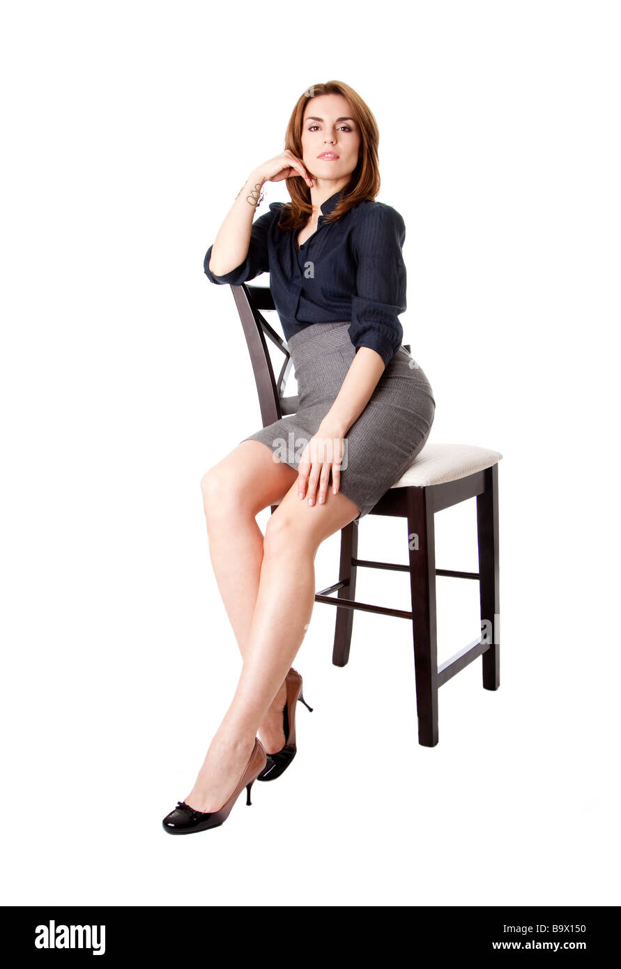 Beautiful sexy brunette business woman sitting wearing gray skirt and blue  blouse with hand on leg isolated