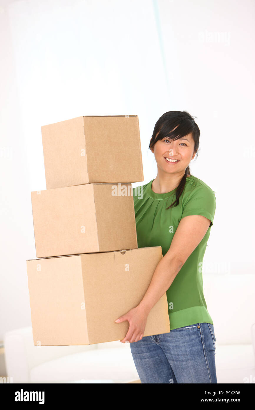 Woman holding stack of boxes - Stock Image